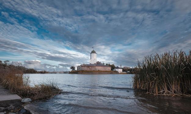 Starożytny zamek w mieście wyborg w rosji z wieżą św.olafa na brzegu zatoki fińskiej wczesną jesienią