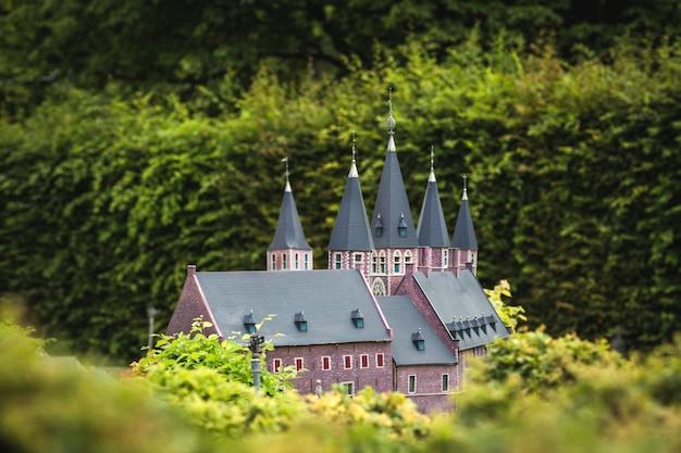 Starożytny zamek z wieloma wieżami otoczony zielenią, miniaturowa scena plenerowa, europa. mini figurki z wysokim rozszczepieniem przedmiotów, realistyczna diorama, model zabawkowy