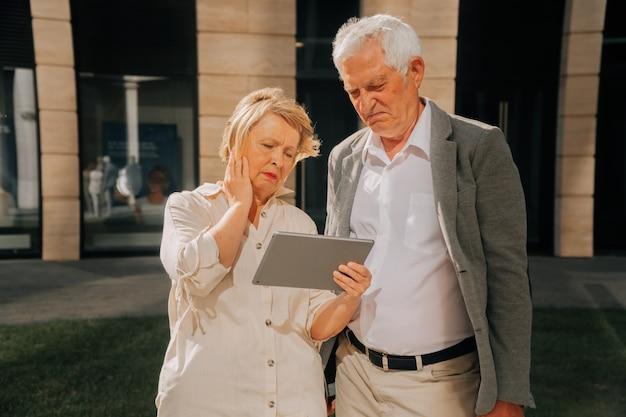 Starsi dziadkowie oglądają wideo na tablecie.