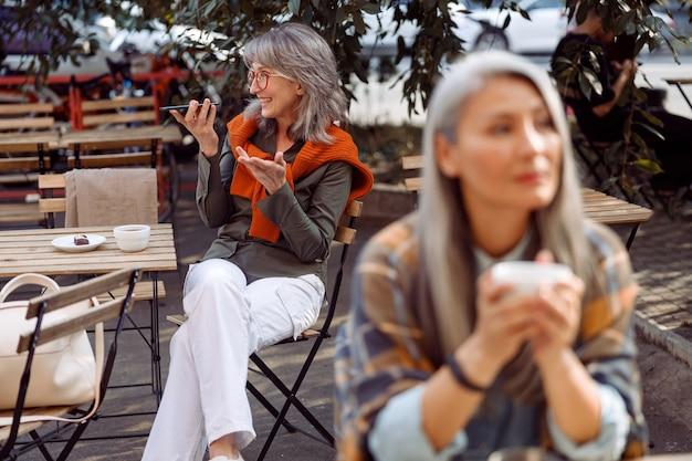 Starsi goście kawiarni koncentrują się na srebrnowłosej kobiecie w okularach nagrywającej wiadomość audio