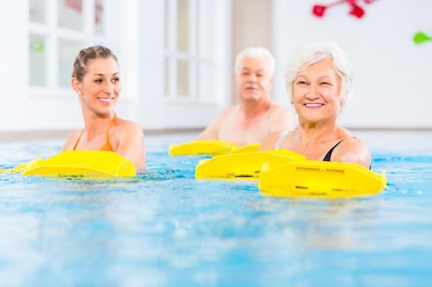 Starsi i młodzi ludzie uprawiający gimnastykę w wodzie z urządzeniem oporowym