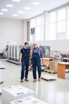 Starsi i młodzi pracownicy drukarni w niebieskich kombinezonach przechodzą przez nowoczesny warsztat i dyskutują o pracy
