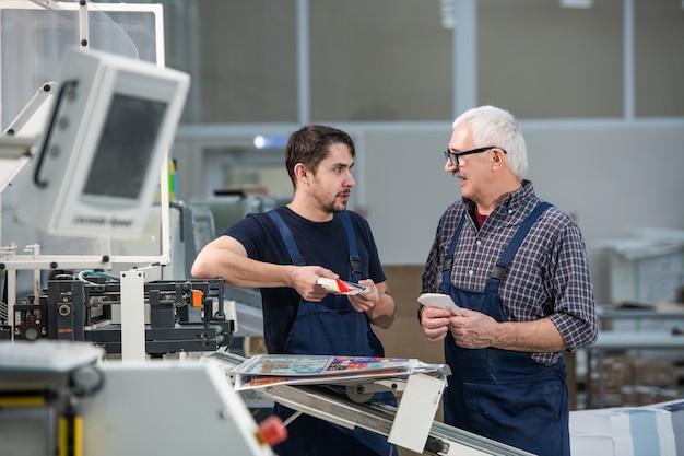Starsi i młodzi pracownicy stoją przy drukarce przemysłowej i omawiają farby drukarskie, obserwując paletę kolorów