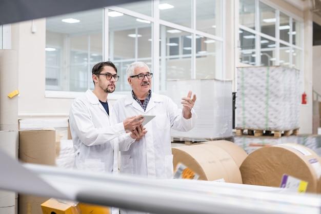 Starsi i młodzi specjaliści laboratoryjni w białych fartuchach używający w fabryce cyfrowego tabletu, rozmawiając o produktywności przemysłowej