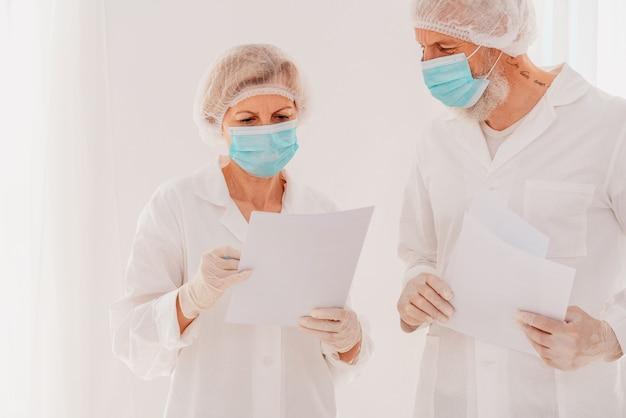 Starsi lekarze z maską na twarz pracują razem w szpitalu