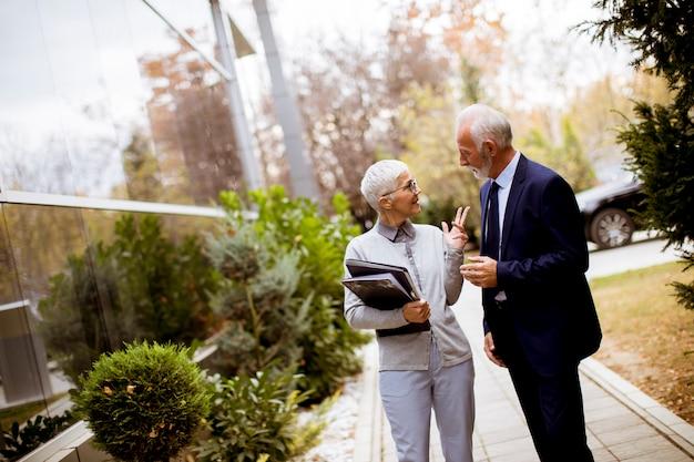 Starsi ludzie biznesu opowiada outdoors i dyskutuje dokument plenerowego