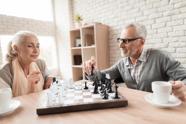 Starsi ludzie grają w szachy w domu opieki.