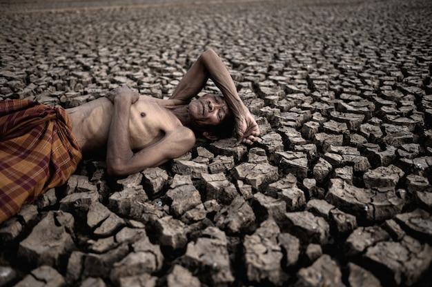 Starsi ludzie leżą płasko na rękach, brzuchu i czole, na suchej ziemi, globalne ocieplenie.