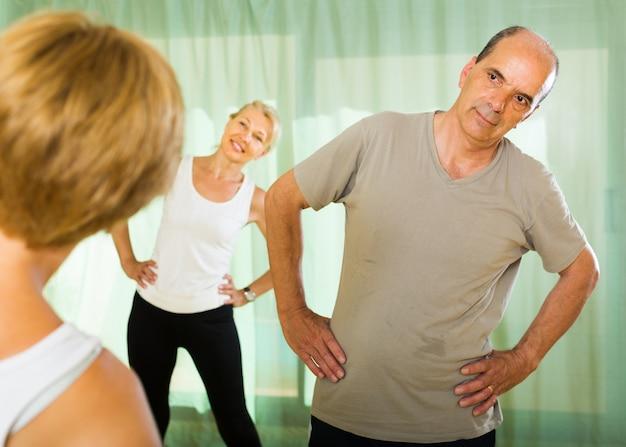 Starsi ludzie na fitness z instruktorem