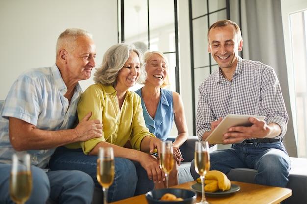 Starsi ludzie oglądający filmy wideo za pomocą tabletu