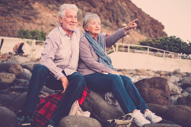 Starsi ludzie razem w miłości - starsza para siedzi na plaży, przytulanie i patrząc i wskazując ręką wyciągniętą w kierunku horyzontu o zachodzie słońca. koncepcja wakacji, czasu wolnego, relaksu