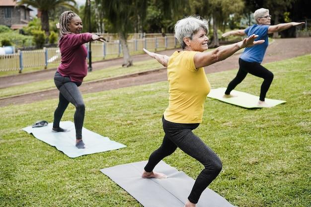 Starsi ludzie robią zajęcia jogi, utrzymując dystans społeczny na świeżym powietrzu w parku miejskim