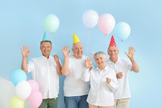 Starsi ludzie świętujący urodziny w pobliżu kolorowej ściany