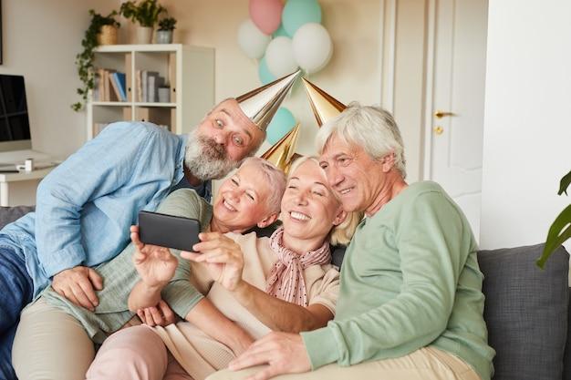 Starsi ludzie w czapkach imprezowych siedząc na kanapie i pozują do kamery razem robią selfie portret na telefon komórkowy