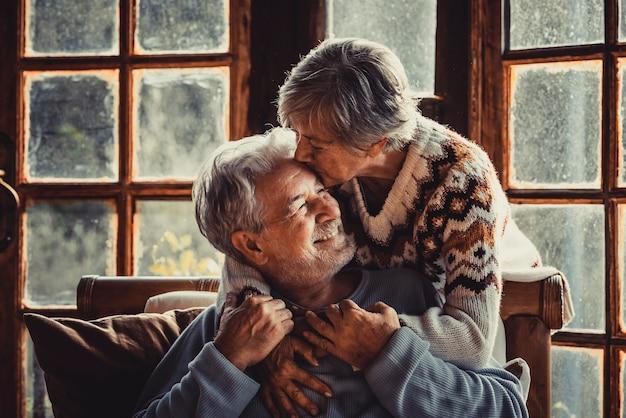Starsi ludzie w domu w miłości całują się i opiekują się sobą. szczęśliwy związek dojrzały mężczyzna i kobieta razem. stary mężczyzna siedzi na kanapie, a starsza kobieta przytula go ostrożnie