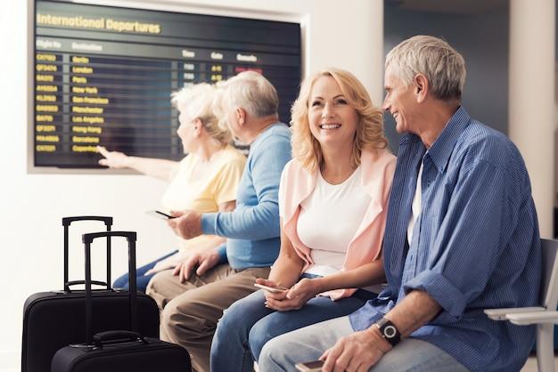 Starsi ludzie w poczekalni na lotnisku.