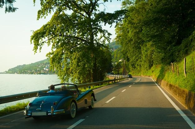 Starsi ludzie w retro samochód jadący po drodze z pięknym letnim krajobrazem. szwajcarski.