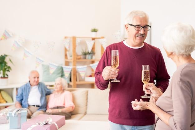 Starsi małżonkowie opiekują się kieliszkami szampana podczas świętowania wakacji z przyjaciółmi