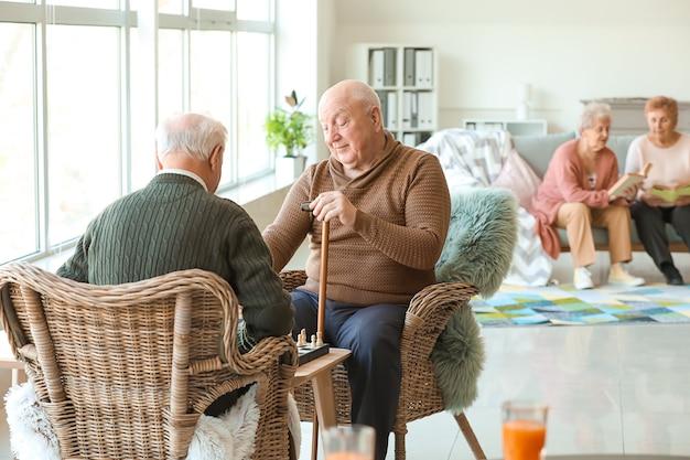 Starsi mężczyźni grają w szachy w domu opieki