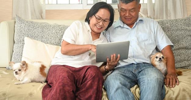 Starsi mężczyźni i kobiety korzystają z wideokonferencji na tabletach i relaksują się w domu z psem chihuahua.