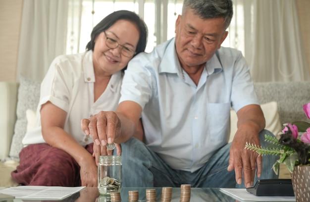 Starsi mężczyźni i kobiety szczęśliwie oszczędzają pieniądze.