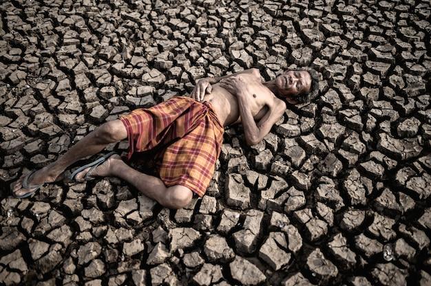 Starsi mężczyźni leżą płasko, z rękami na brzuchu na suchej i popękanej ziemi, globalne ocieplenie