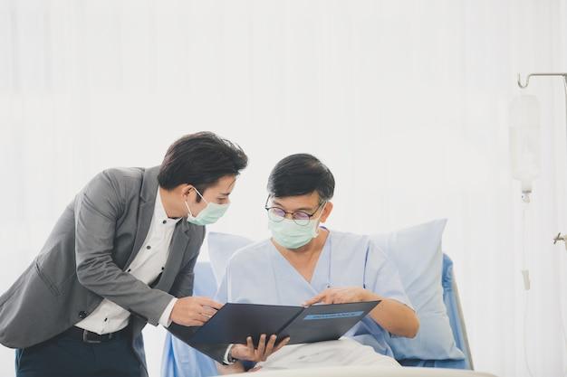 Starsi mężczyźni leżący na łóżku na szpitalnym spotkaniu z doradcą finansowym, starsza kobieta czytająca kontrakt, oboje nosili maski higieniczne, aby zapobiec epidemiom chorób.