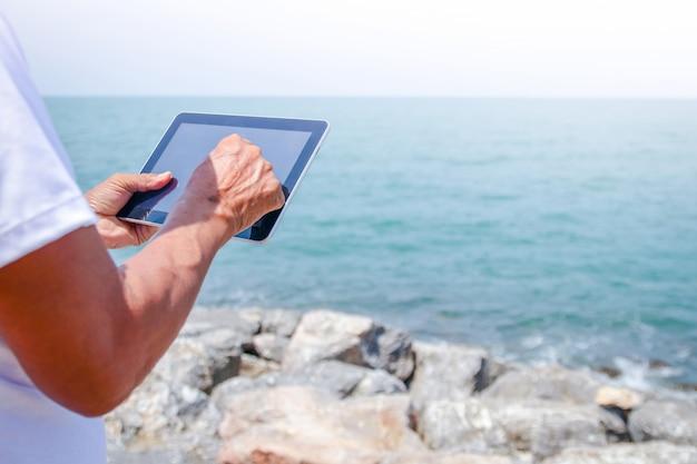 Starsi mężczyźni używają tabletów do grania w internecie w celu łączenia się z ludźmi. przyszedł odpocząć nad morzem.