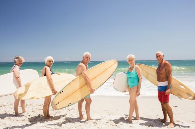 Starsi przyjaciele trzyma deskę surfingową