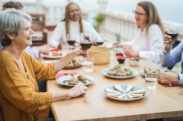Starsi wielorasowi ludzie bawią się pijąc wino podczas kolacji na patio - skup się na lewej twarzy kobiety