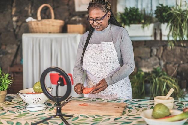Starsza afroamerykanka przesyła strumieniowo wideo na żywo do obserwatorów w mediach społecznościowych, trzymając marchewkę - świeża i zdrowa żywność