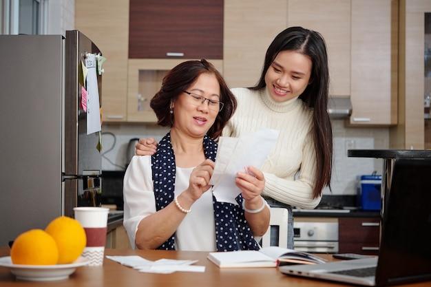 Starsza azjatka i jej dorosła córka rozmawiają o rachunkach za media, które muszą płacić online, siedząc przy stole kuchennym