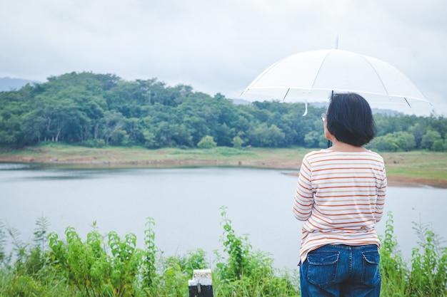 Starsza azjatka trzyma biały parasol, aby zapobiec deszczowi. stojąc i obserwując naturalny widok gór w porze deszczowej