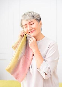Starsza azjatka trzymająca szalik blisko twarzy w domu