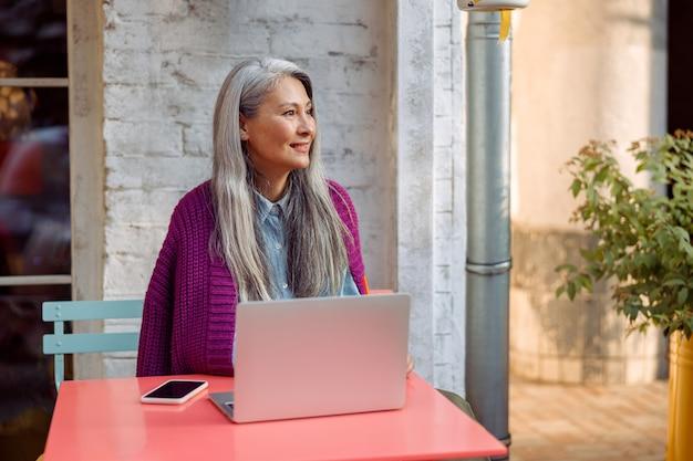 Starsza azjatycka dama w dzianinowej kurtce ze smartfonem i laptopem siedzi przy stole na tarasie