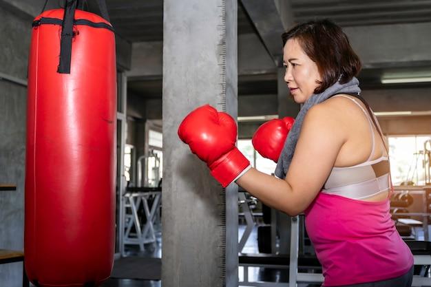 Starsza azjatycka gruba kobieta trenuje boks przy sprawności fizycznej gym.