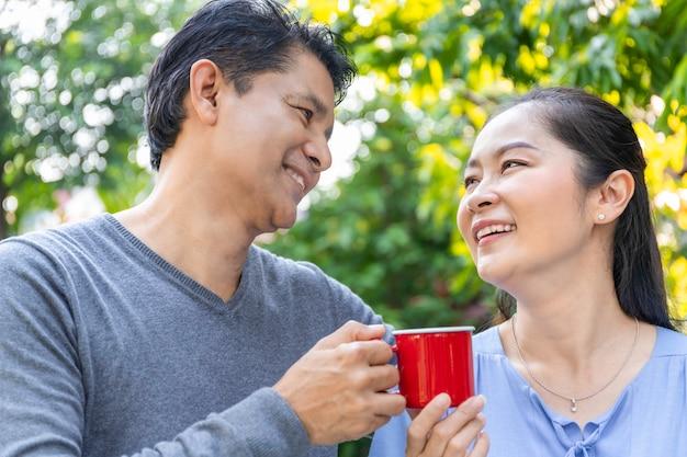 Starsza azjatycka para pije kawę przy ogródem.