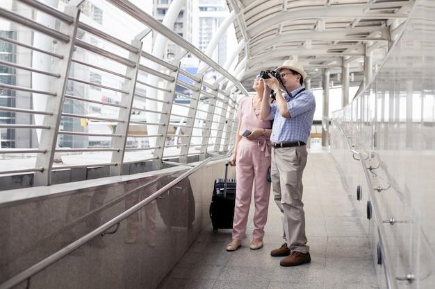 Starsza azjatycka para z mężczyzna przestaje robić zdjęcia i szczęśliwie uśmiecha się na lotnisku.