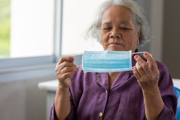 Starsza azjatykcia kobieta jest ubranym twarzy maskę podczas korona słoneczna wybuchu wirusa i grypy. choroba i ochrona przed chorobami. starzejąca się pacjentka narażona na ryzyko zakażenia wirusem koronowym [covid-19].