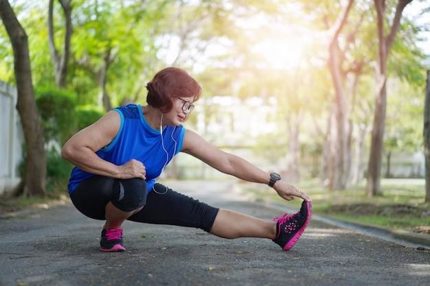 Starsza azjatykcia kobieta rozciąga mięśnie przy parkowym i słuchającym muzyka.