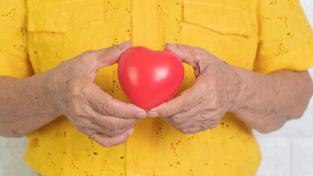 Starsza azjatykcia kobiety mienia czerwieni serce. koncepcja samotności i powinna być pod opieką dzieci i bliskich