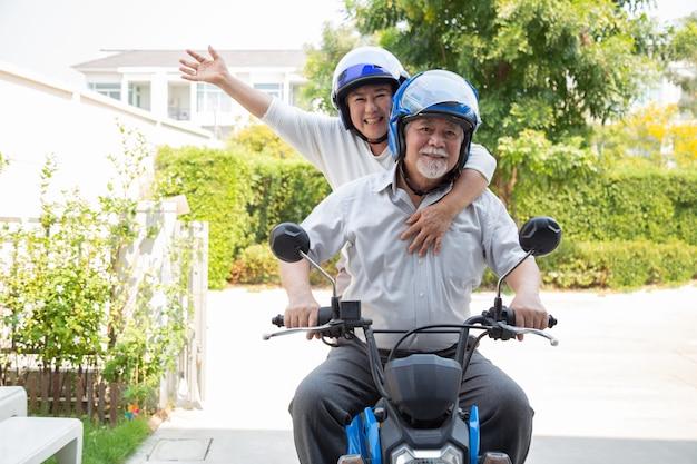 Starsza azjatykcia para jedzie motocykl, szczęśliwy aktywny starości i stylu życia pojęcie