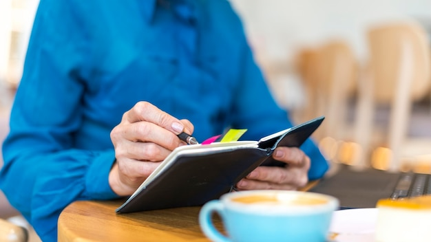 Starsza biznesowa kobieta pracuje na laptopie i pisze w porządku obrad