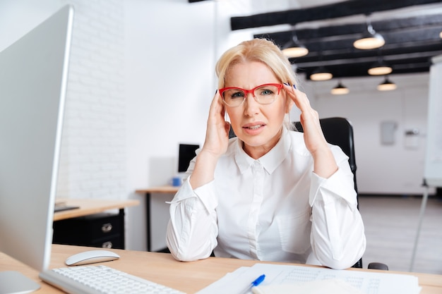 Starsza bizneswoman siedzi w swoim miejscu pracy i myśli o pracy w biurze