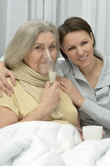 Starsza chora kobieta z troskliwą córką w domu