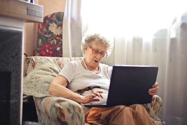 Starsza dama używa laptop