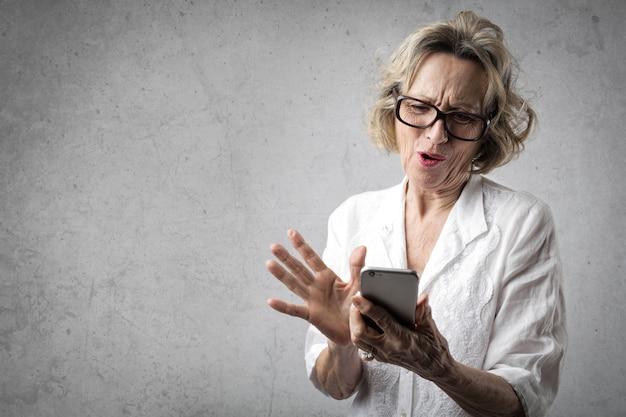 Starsza dama używa smartphone