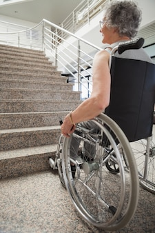 Starsza dama w wózku inwalidzkim przyglądającym up schodku