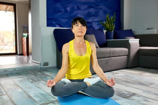 Starsza dojrzała kobieta, siedzi w pozycji lotosu na macie do jogi