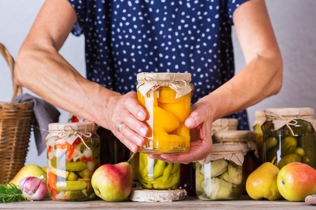 Starsza dojrzała kobieta trzyma w rękach słoik z domowej roboty konserwowane i sfermentowane jedzenie. odmiana marynowanych i marynowanych warzyw, kompot owocowy. gospodarstwo domowe, ekonomika domu, konserwacja zbiorów